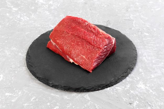 Rohes rindfleischfleisch: frisches schweinefleisch großes filet auf schiefersteinplatte