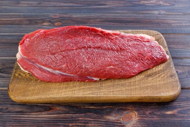 Rohes rindfleischfleisch: großes filet des frischen rindfleischschweines auf hölzernem brett