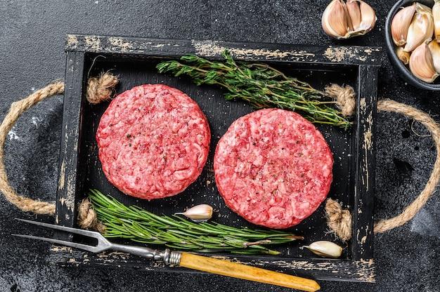 Rohes rindfleischfleisch pastetchen für burger aus hackfleisch und kräutern auf einem holzbrett