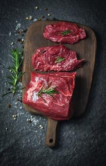 Rohes rindfleischsteak mit kraut und gewürzen - frischfleischrindfleisch geschnitten auf hölzerner schneidebrettoberfläche