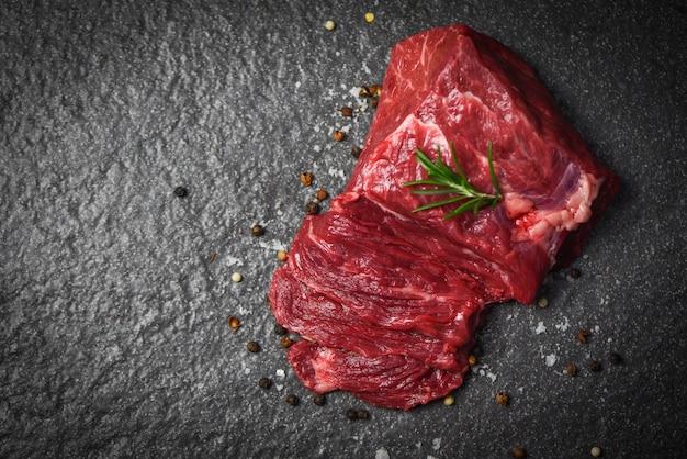 Rohes rindfleischsteak mit kraut und gewürzen - frischfleischrindfleisch geschnitten auf schwarzem hintergrund