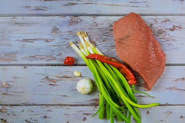 Rohes rindfleischsteakfleisch mit kräutern und gewürzen auf einem hölzernen schneidebrett