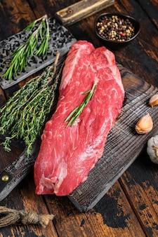 Rohes rock machete rindfleisch fleischsteak auf einem schneidebrett mit hackmesser. dunkler hölzerner hintergrund. draufsicht.