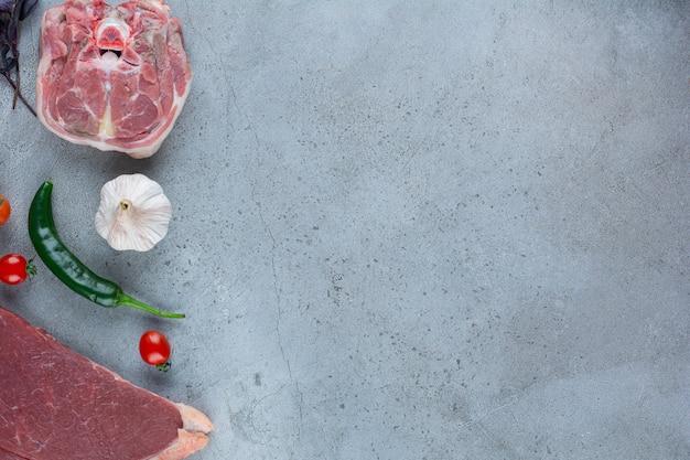 Rohes rotes fleischsteak und gemüse auf steintisch.