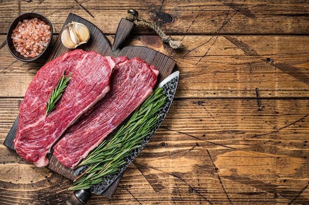 Rohes rump cap steak oder picanha steak auf holzbrett mit metzgermesser. holztisch. draufsicht.