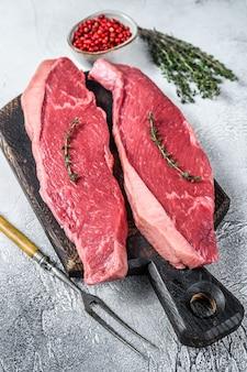 Rohes rumpf- oder picanha-steak auf einem hölzernen schneidebrett. weißer hintergrund. draufsicht.