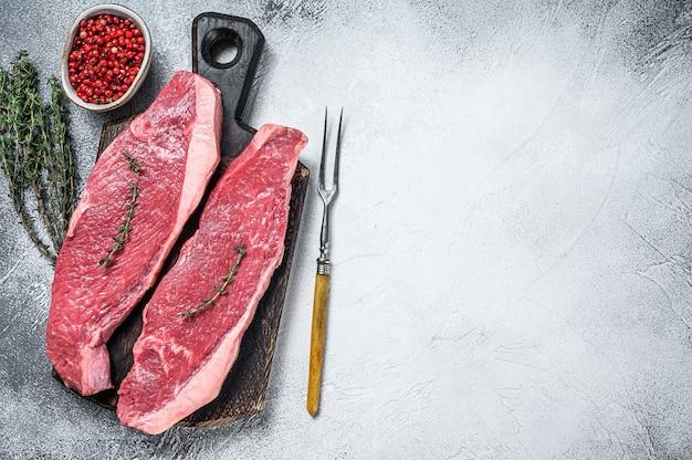 Rohes rumpf- oder picanha-steak auf einem hölzernen schneidebrett