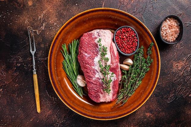 Rohes rundes rindfleischfleisch zum braten auf einem rustikalen teller mit kräutern