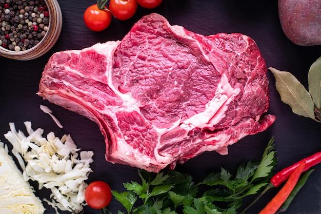 Rohes saftiges fleischsteak bereit zum grillen auf einem schwarzen schieferbrett. steak mit knochen, kalbfleisch auf einem holzbrett mit kirschtomaten, peperoni und kräutern. ansicht von oben