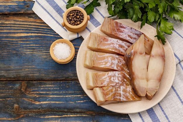 Rohes saithe-filet. frische scheiben auf einem teller, gewürze, petersilie. ein paar grüns, vintage-serviette