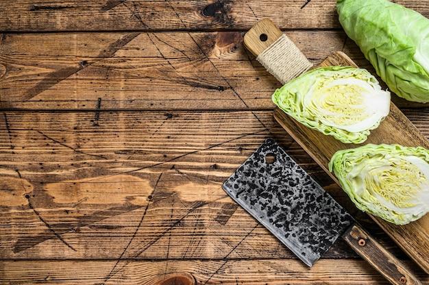 Rohes schneiden spitzkohlkopf auf einem schneidebrett. holzhintergrund