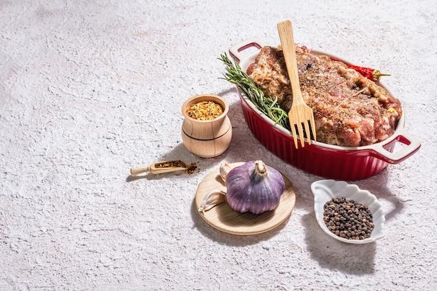 Rohes schweinebrötchen gefüllt mit knoblauch und karotten in einer keramikbratform.