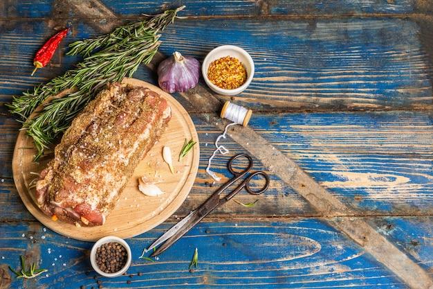 Rohes schweinebrötchen gefüllt mit knoblauch und karotten