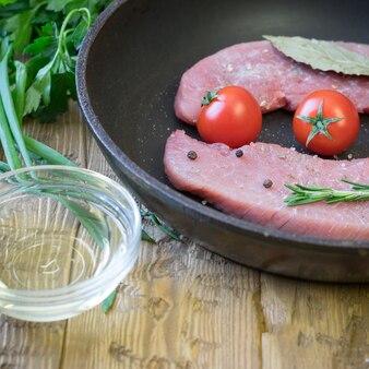 Rohes schweinefleisch auf einer bratpfanne auf einer rustikalen tabelle.