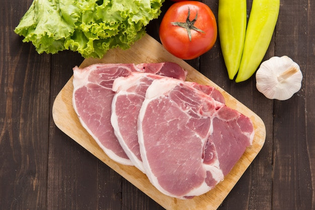 Rohes schweinefleisch auf schneidebrett und gemüse auf holztisch
