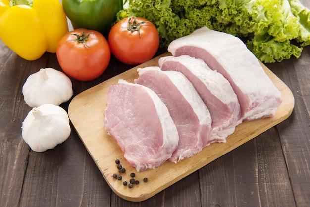 Rohes schweinefleisch auf schneidebrett und gemüse.