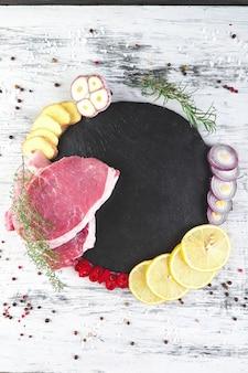 Rohes schweinefleisch auf schwarzer schieferplatte mit gewürzbestandteil