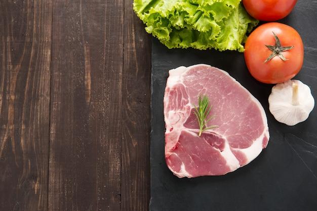 Rohes schweinefleisch der draufsicht auf tafel und gemüse auf holztisch