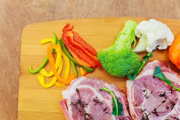 Rohes schweinefleisch in marinade, auf einem schneidebrett mit tomatenzweig, messer für fleisch- und gewürzgrenze, text aus holz im rustikalen hintergrund von oben anzeigen