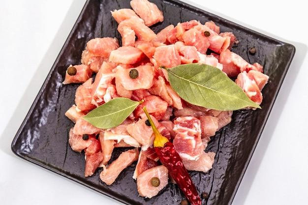Rohes schweinefleisch in würfel geschnitten mit trockenen lorbeerblättern und chili