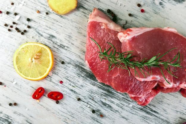 Rohes schweinefleisch mit gewürzbestandteil - rosmarin, ingwer, paprikapfeffer, zwiebel. ansicht von oben. flach liegen. kopieren sie platz.