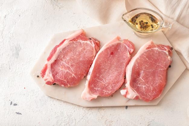 Rohes schweinefleisch mit öl auf dem tisch