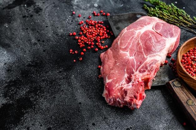 Rohes schweinefleischmarmorsteak auf einem fleischerbeil. schwarzer hintergrund. draufsicht. speicherplatz kopieren.