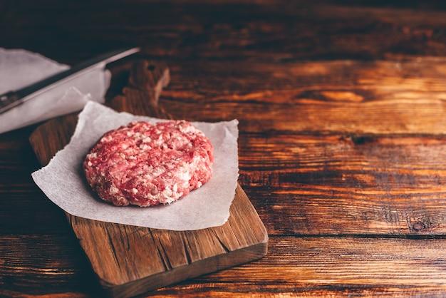 Rohes schweinefleischpastetchen für burger auf schneidebrett und wachspapier. kopieren sie das feld rechts.
