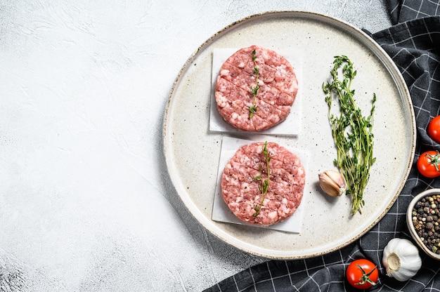 Rohes schweinefleischpastetchen, hackfleischkoteletts auf einem schneidebrett. bio-hackfleisch. grauer hintergrund. draufsicht. speicherplatz kopieren.
