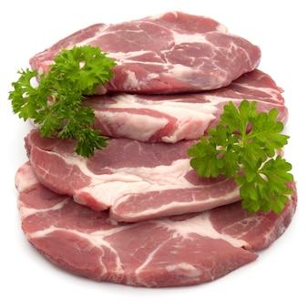 Rohes schweinehals-kotelettfleisch mit petersilienkrautblättern garnieren lokalisiert auf weißem hintergrundausschnitt