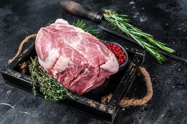 Rohes schweinehalsfleischstück für chopsteak in holztablett mit kräutern. schwarz