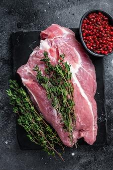 Rohes schweineschulterfleisch, das auf einem marmorbrett geschnitten wird