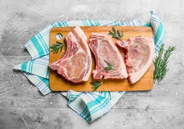 Rohes schweinesteak am knochen mit rosmarin auf der serviette. auf einer rustikalen oberfläche.