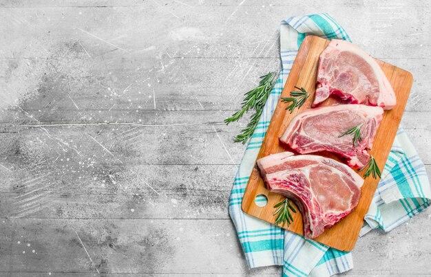 Rohes schweinesteak auf dem knochen mit rosmarin auf der serviette auf einem rustikalen tisch.