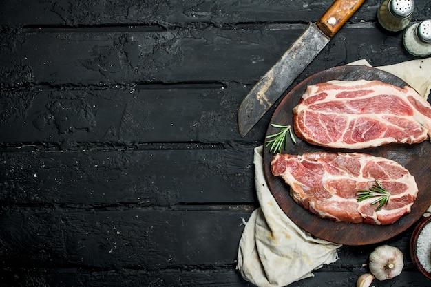 Rohes schweinesteak mit einem alten messer auf einem schneidebrett. auf einem schwarzen rustikalen hintergrund.