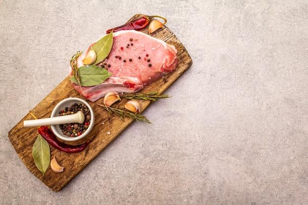 Rohes schweinesteak mit gewürzen und getrockneten kräutern auf vintage-holzbrett. salz, knoblauch, paprika, rosmarin, lorbeerblatt mit keramikmörser und stößel auf steinhintergrund, draufsicht
