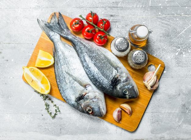 Rohes seefisch-dorado mit tomaten, zitronenschnitzen und gewürzen. auf einem rustikalen.