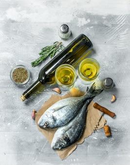 Rohes seefisch-dorado mit weißwein und gewürzen auf einem rustikalen tisch.