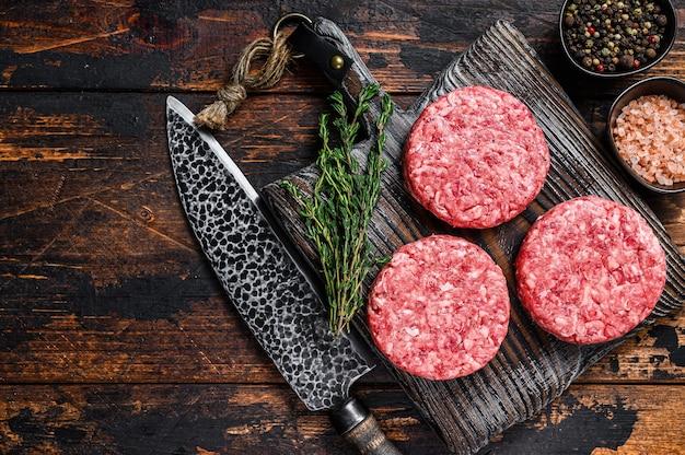 Rohes steak burger pastetchen mit rinderhackfleisch und thymian auf einem hölzernen schneidebrett
