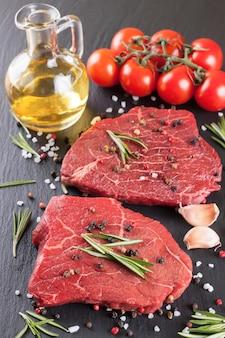 Rohes steak mit, gewürzen und zutaten zum kochen.