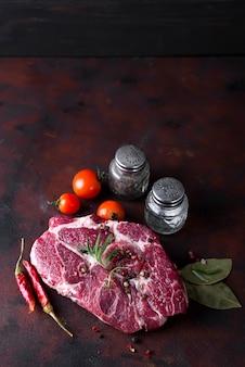 Rohes steak mit gewürzen und zutaten zum kochen.