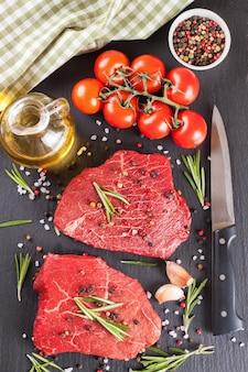 Rohes steak mit messer, gewürzen und zutaten zum kochen.