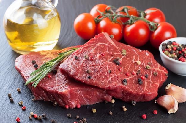 Rohes steak mit rosmarin, salz und pfeffer auf schieferplatte.