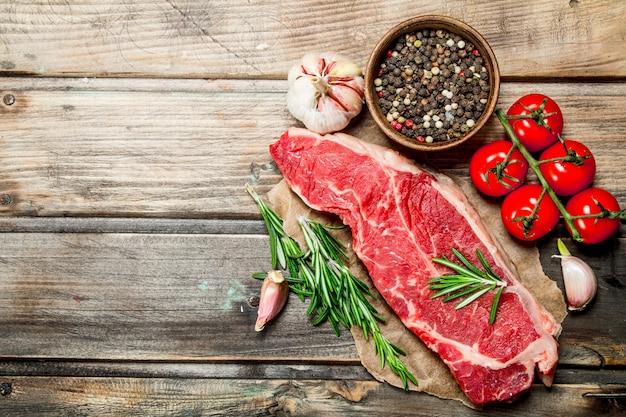 Rohes steak mit rosmarin, tomaten und aromatischen gewürzen auf holztisch.