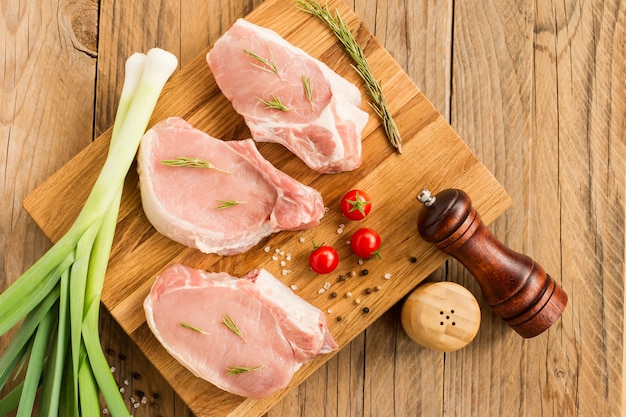 Rohes steak von jungem schweinefleisch auf einem küchenbrett und einem holztisch mit zwiebelgrün, rosmarin, tomaten.