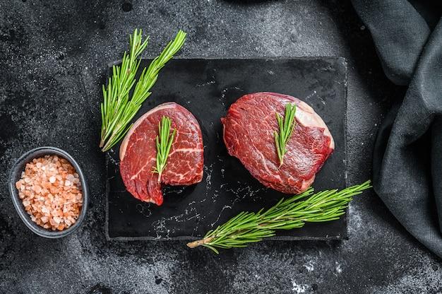 Rohes steakfiletfilet auf einem steinbrett. schwarzer hintergrund.