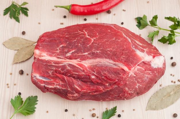 Rohes stück rindfleisch mit gewürzen und petersilie auf dem tisch