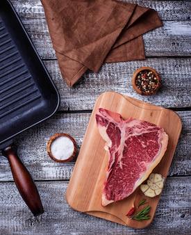 Rohes t-bone-steak und grillpfanne aus eisen