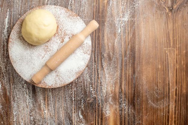 Rohes teigstück der draufsicht mit mehl auf hölzernem schreibtischmehlmehlbackteig