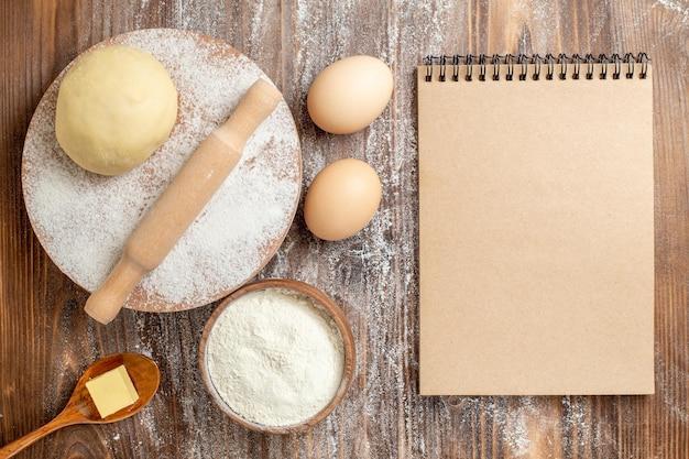 Rohes teigstück der draufsicht mit mehl und eiern auf hölzernem schreibtischmehlbackteig